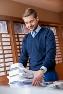 Smiling worker stacking button down shirts in menswear shopの写真素材 [FYI02172390]