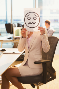 Portrait of businesswoman holding frowning face printout over her face in officeの写真素材 [FYI02172403]