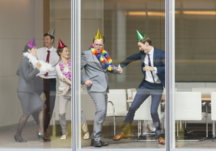 Playful business people in party hats dancing at conference room windowの写真素材 [FYI02172410]