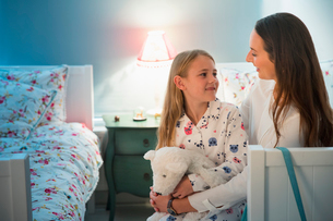 Mother and daughter talking at bedtime in bedroomの写真素材 [FYI02172421]