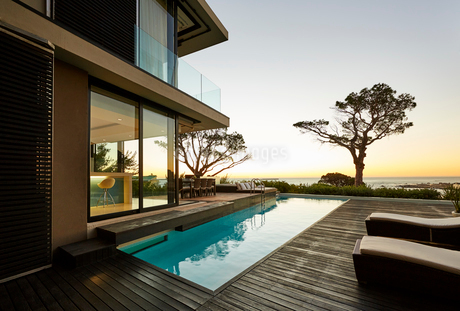 Modern luxury home showcase patio and swimming pool with sunset ocean viewの写真素材 [FYI02172433]