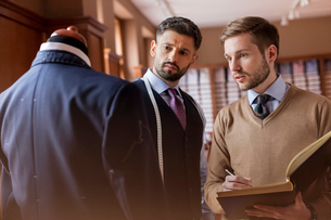 Tailors discussing suit and taking notes in menswear shopの写真素材 [FYI02172436]