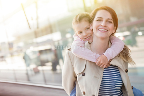 Portrait smiling mother piggybacking daughter outside airportの写真素材 [FYI02172450]