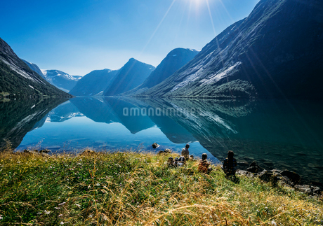 Friends relaxing at sunny tranquil mountain lakeside, Norwayの写真素材 [FYI02172462]