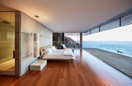 Modern luxury bedroom open to patio with ocean viewの写真素材 [FYI02172475]