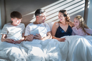 Smiling family laying in bed using digital tabletの写真素材 [FYI02172477]