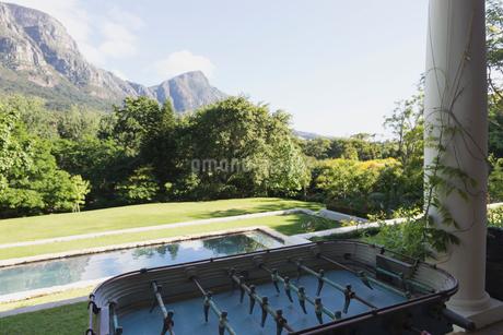Foosball table on luxury patio overlooking swimming pool and mountainの写真素材 [FYI02172488]