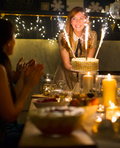 Enthusiastic woman serving cake with sparkler fireworks to clapping friendsの写真素材 [FYI02172523]