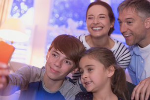 Smiling family taking selfie with camera phoneの写真素材 [FYI02172560]