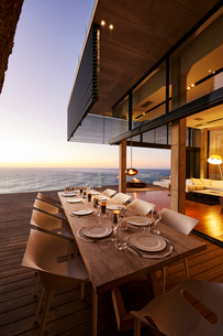 Luxury modern dining table with sunset ocean viewの写真素材 [FYI02172572]