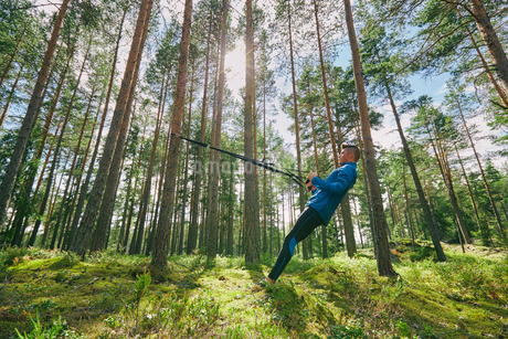 Runner stretching with resistance band on tree in woodsの写真素材 [FYI02172580]