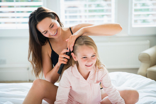 Mother brushing daughter's hair on bedの写真素材 [FYI02172611]
