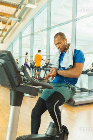 Man checking smart watch on exercise bike at gymの写真素材 [FYI02172628]