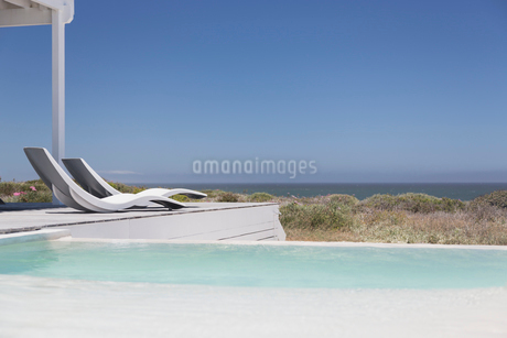 Swimming pool and modern lounge chairs overlooking ocean view under sunny blue skyの写真素材 [FYI02172644]