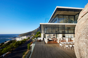 Modern luxury house and patio with ocean view under sunny blue skyの写真素材 [FYI02172646]