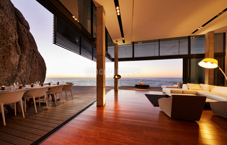 Modern luxury living room open to patio with sunset ocean viewの写真素材 [FYI02172653]
