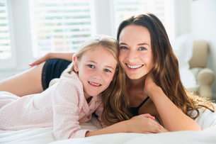 Portrait smiling mother and daughter laying on bedの写真素材 [FYI02172662]