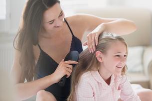 Mother brushing daughter's hairの写真素材 [FYI02172664]