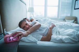 Man in bed turning off morning alarm clockの写真素材 [FYI02172678]