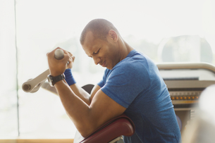 Man doing biceps curls one exercise equipment at gymの写真素材 [FYI02172681]