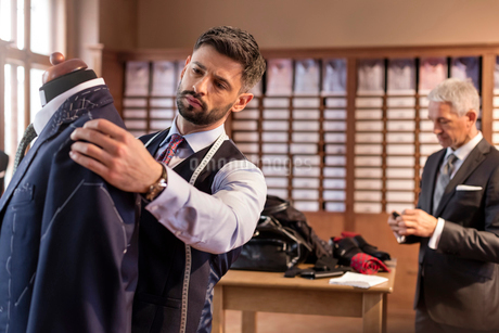 Tailor adjusting suit on dressmakers model in menswear shopの写真素材 [FYI02172683]
