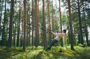 Runner using resistance band on tree in woodsの写真素材 [FYI02172693]