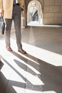 Corporate businessman walking in sunny cloisterの写真素材 [FYI02172702]