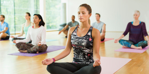 Serene woman in lotus position with eyes closed in yoga classの写真素材 [FYI02172715]