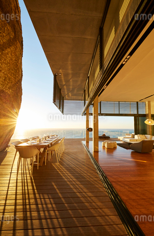 Dining table on modern luxury patio with sunset ocean viewの写真素材 [FYI02172723]