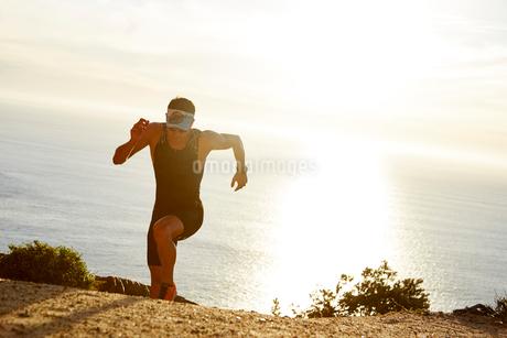 Male triathlete runner running uphill on sunny ocean trailの写真素材 [FYI02172729]
