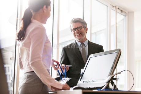 Businessman showing credentials to businesswoman at front deskの写真素材 [FYI02172735]