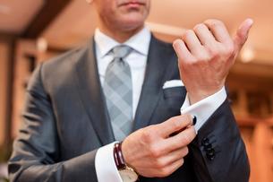 Close up well-dressed businessman adjusting cufflinksの写真素材 [FYI02172754]