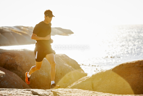 Male triathlete running on rocky trail along sunny oceanの写真素材 [FYI02172774]