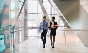 Corporate businessman and businesswoman walking and talking in modern office lobbyの写真素材 [FYI02172775]