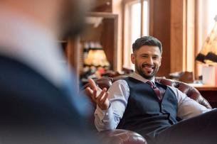 Smiling businessman gesturing in menswear shopの写真素材 [FYI02172797]