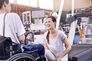 Smiling physical therapist talking to man in wheelchairの写真素材 [FYI02172801]