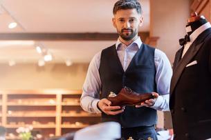 Portrait confident businessman holding dress shoe in menswear shopの写真素材 [FYI02172888]