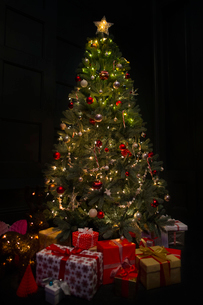 Illuminated Christmas tree surrounded by gifts in dark roomの写真素材 [FYI02172901]