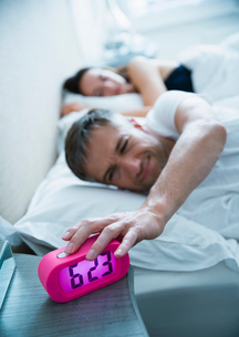 Man in bed turning off morning alarm clockの写真素材 [FYI02172903]