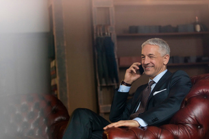 Smiling businessman talking on cell phone in menswear shopの写真素材 [FYI02172907]