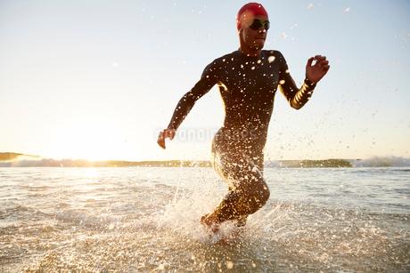 Male triathlete swimmer in wet suit running from oceanの写真素材 [FYI02172910]