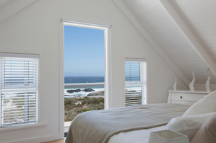 Vaulted ceiling in white home showcase bedroom with sunny ocean viewの写真素材 [FYI02172958]