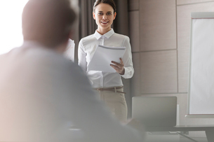 Businesswoman with paperwork leading meeting in conference roomの写真素材 [FYI02172975]