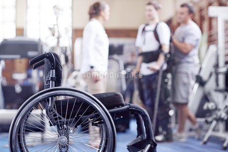 Man receiving physical therapy with wheelchair in foregroundの写真素材 [FYI02172982]