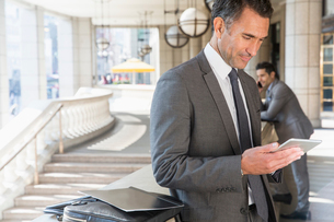 Corporate businessman using digital tablet outdoorsの写真素材 [FYI02172999]