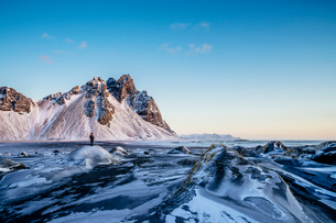 Woman standing among remote, icy landscape, Hofn, Icelandの写真素材 [FYI02173005]
