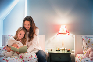 Mother and daughter reading book in bedroomの写真素材 [FYI02173006]