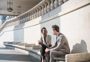 Corporate businessman and businesswoman enjoying coffee break on sunny stairsの写真素材 [FYI02173012]