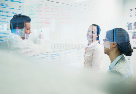 Business people brainstorming at whiteboard in officeの写真素材 [FYI02173020]