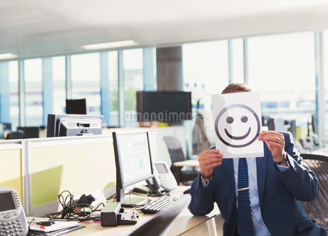 Portrait of businessman holding smiley face printout over his face in officeの写真素材 [FYI02173028]
